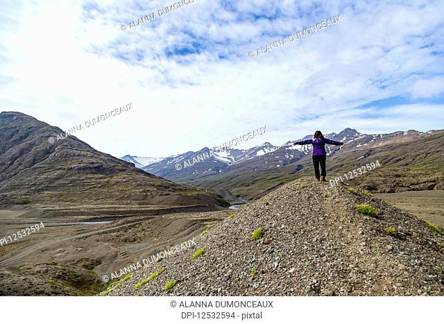 A female hiker celebrates nature with her arms outstretched at the peak of a hill in the mountain landscape of Southern Iceland; Iceland