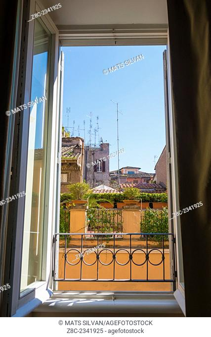 Window view over patio with antenna in Rome, Italy