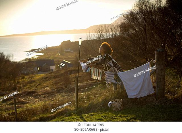 Woman hanging out washing in garden, Tokavaig, Isle of Skye, Scotland