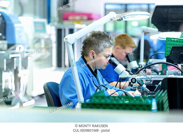 Female worker soldering component onto circuit boards in circuit board assembly factory