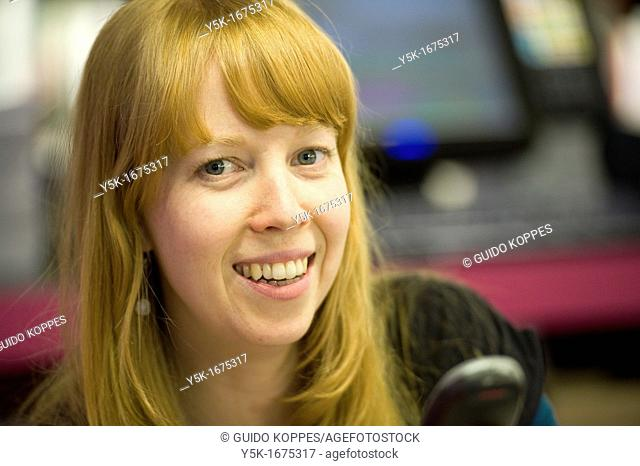 Rotterdam, Netherlands. Young, attractive and redheaded woman, working full of joy, in a museum bookstore