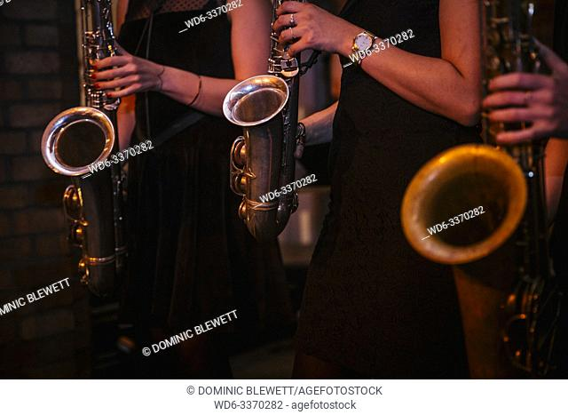 Young women play the saxophone in a band