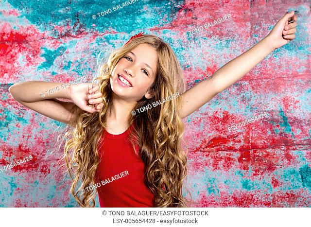 Blond happy kid girl in red happy with arms up in grunge background