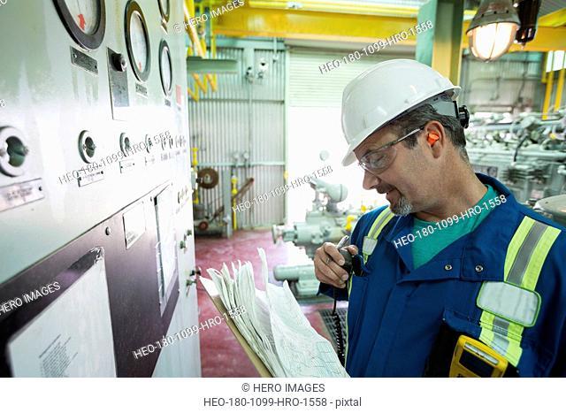 Male worker using walkie-talkie in gas plant