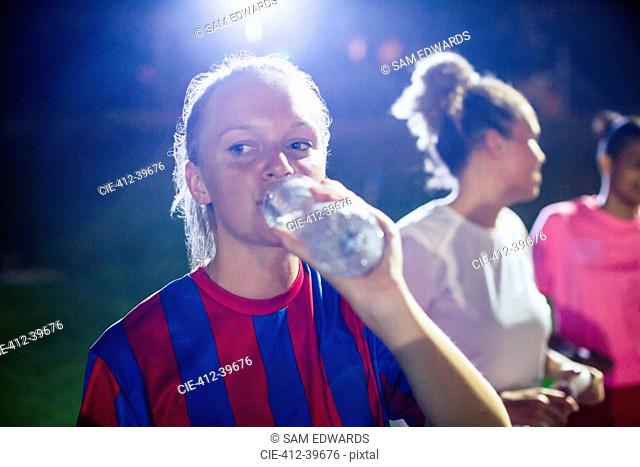 Young female soccer player drinking from water bottle