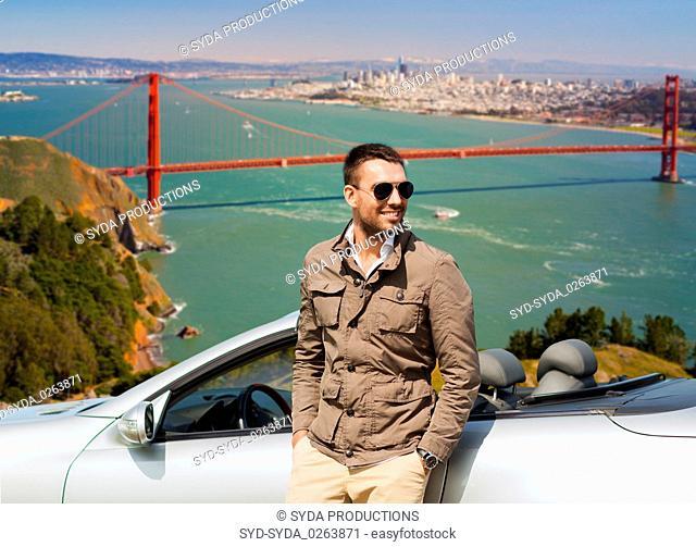 man at convertible car over golden gate bridge