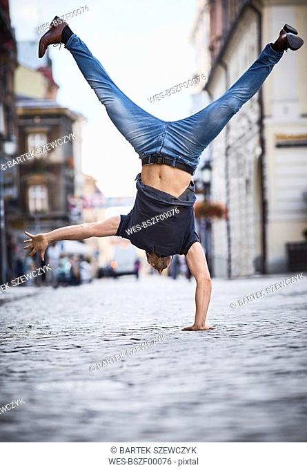 Man doing a handstand in the city