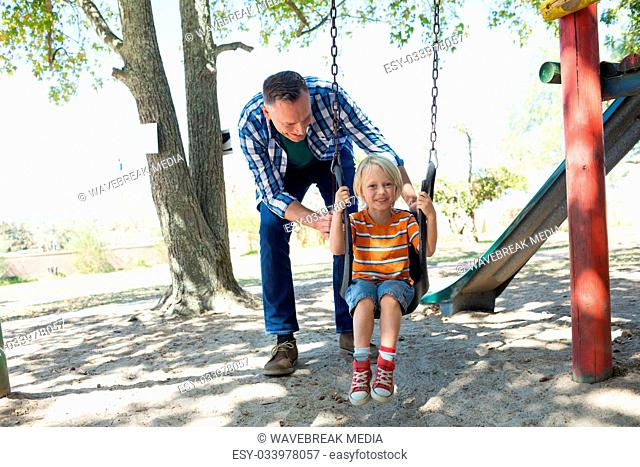 Father pushing son sitting on swing