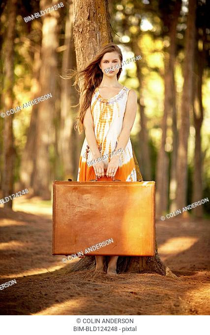 Caucasian woman carrying suitcases in forest