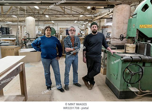 Portrait of a team of three mixed race carpenters in a large woodworking factory