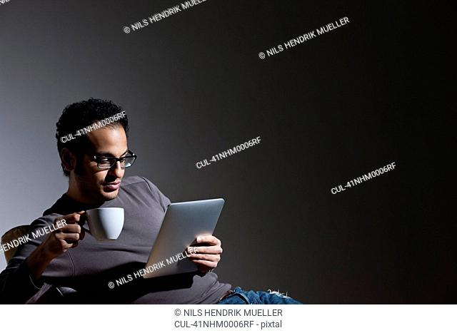 Man with coffee using tablet computer