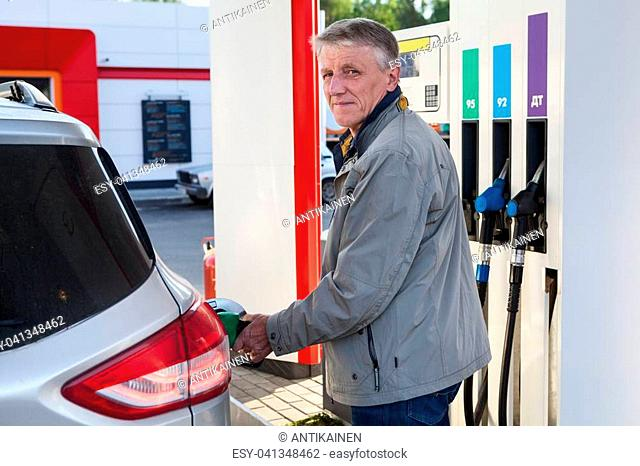 Portrait of European mature man refueling own car on gas station at summer