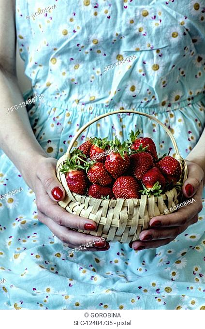 A woman holding a basket of fresh strawberries