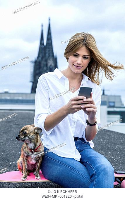 Germany, Cologne, portrait of young woman sitting on roof terrace besides her dog looking at smartphone