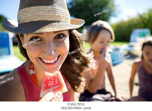 Portrait smiling mother and children eating watermelon on sunny summer beach