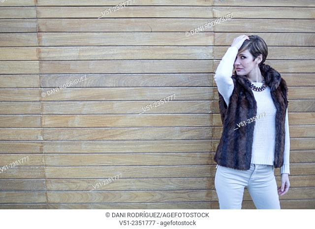 Portrait of a stylish woman outdoors looking at camera and touching her hair