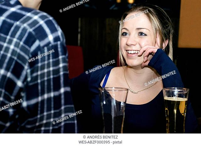 Smiling woman talking with a man in a bar