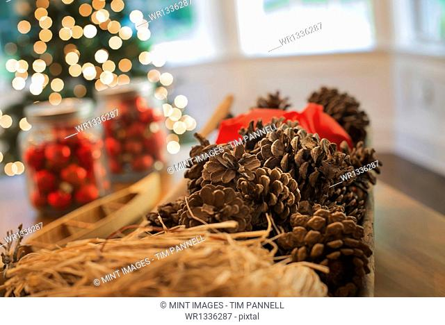 Red glass balls and pine cones. Christmas decorations and a Christmas tree