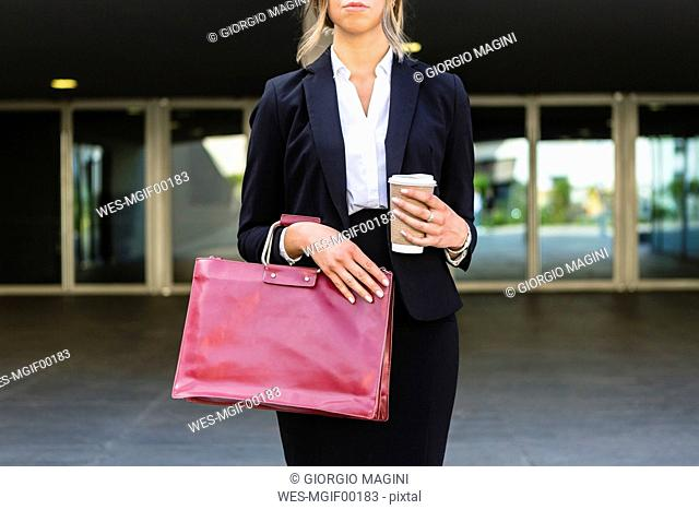 Businesswoman with fashionable red leatherbag and coffee to go, partial view