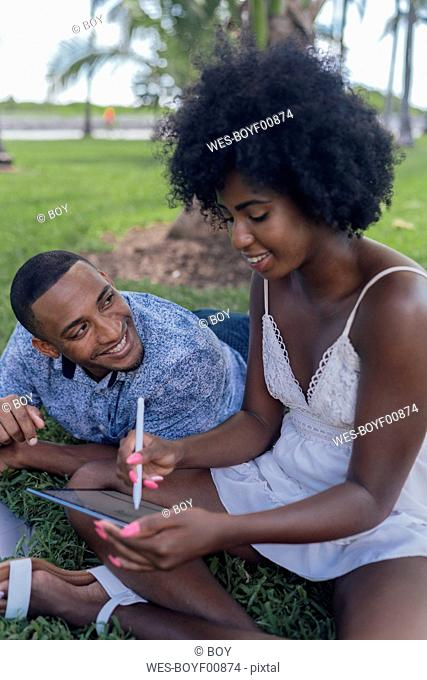 USA, Florida, Miami Beach, smiling young man looking at girlfriend using tablet on lawn in a park