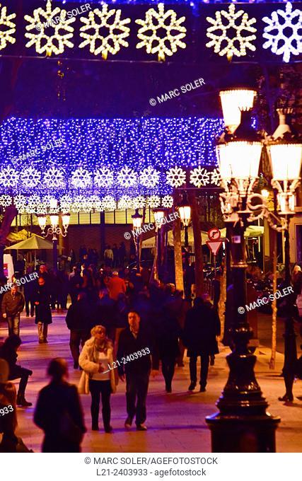 Christmas neon lights on at night. People walking on a street. Barcelona, Catalonia, Spain