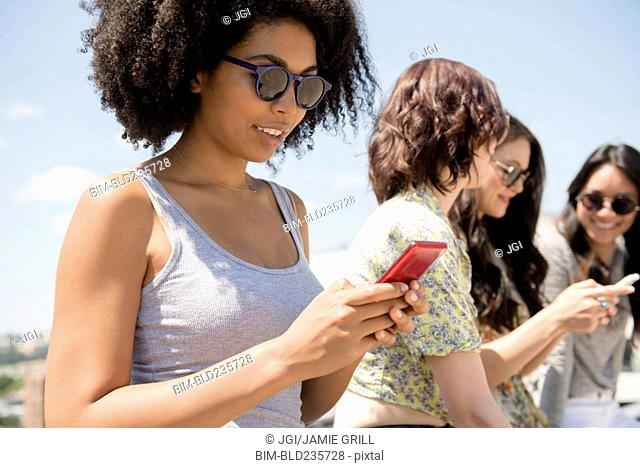 Women texting on cell phones outdoors