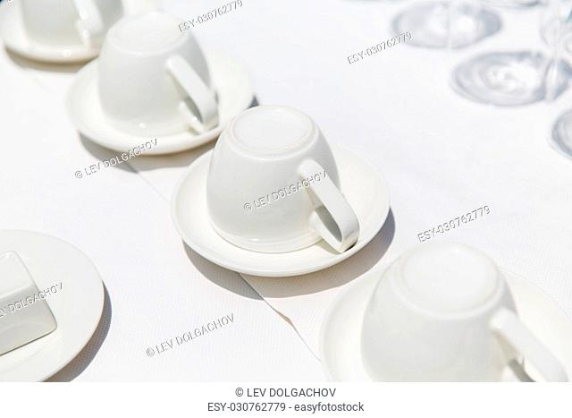 dishes, crockery and porcelain concept - white coffee cups upside down on saucers