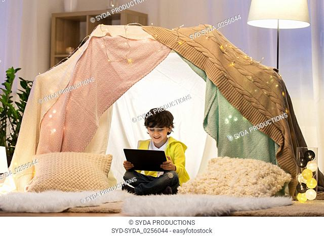 little boy with tablet pc in kids tent at home