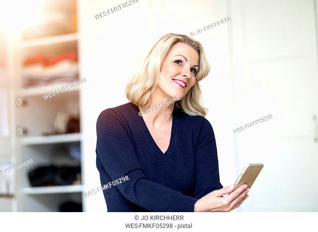 Portrait of smiling blond woman using smartphone at home