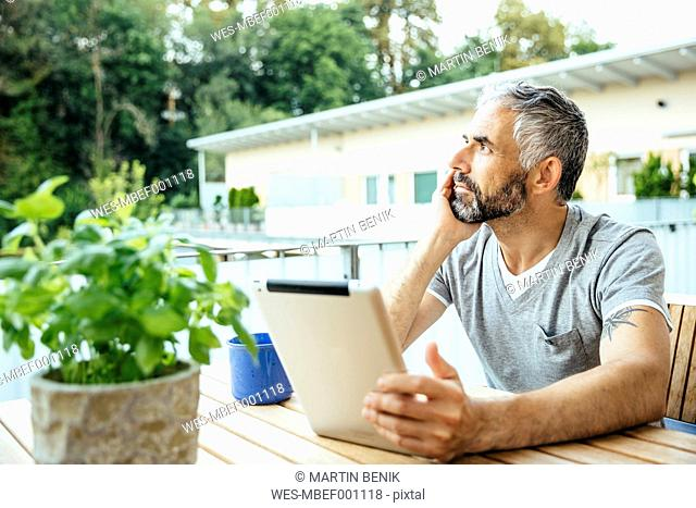 Pensive man with digital tablet sitting on his balcony