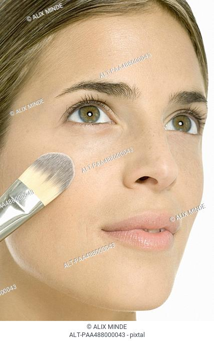 Woman putting on blush, close-up of face