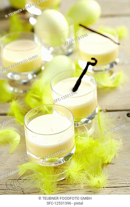 Vanilla eggnog in glasses for Easter, decorated with yellow feathers and Easter eggs