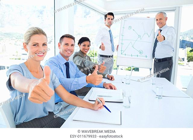 Business team smiling at camera showing thumbs up