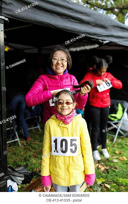 Portrait smiling, confident mother and daughter runners at charity run tent