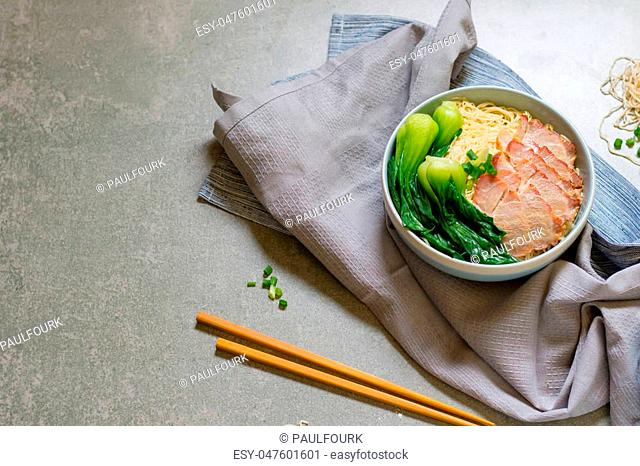 delicious egg noodle with red pork and vegetable in bowl decoration with chopstick on table,thaifood,selective focus