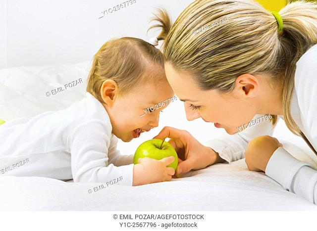 Mather and baby together with green apple in hands