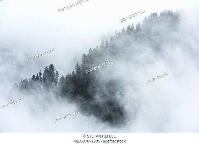 Misty mood in the Dolomite Alps with telephoto lens, Italy