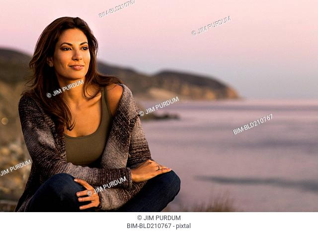 Woman wrapped in sweater on beach