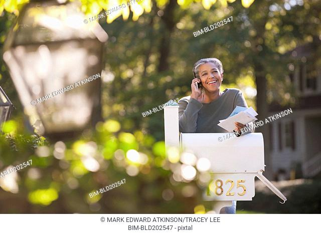 Mixed race woman holding mail and talking on cell phone