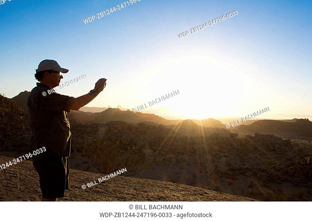 Namibia Africa sunset tourists taking photos at Damaraland at resort called Mowani Mountain Camp with beautiful rock formations