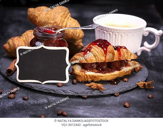 baked crispy croissants with raspberry jam and black empty wooden plaque, black background