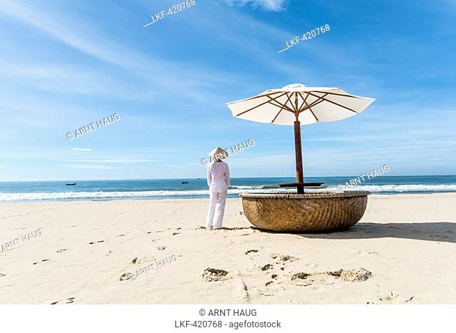 Woman wearing typical clothes and straw hat looking out to sea towards fishing boats, coast of Mui Ne, south Vietnam, Vietnam, Asia