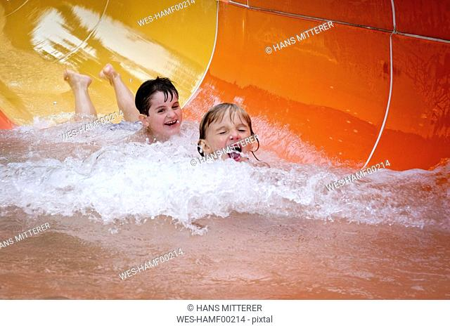 Two boys having fun on water slide