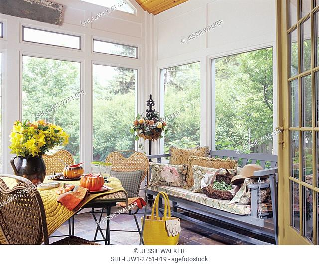 PORCH/ SUNROOM: Glider with pillows, basket of green beans, sunhat, garden cafe table and chairs set with ceramic pumpkin soup bowls