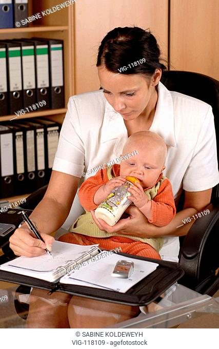 Employed mother carrying a baby and writing a notice in her documents.  - GERMANY, 12/07/2005