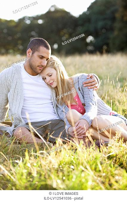 A young couple sitting on the grass, embracing