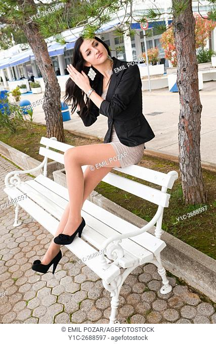 Sitting atop White bench young woman