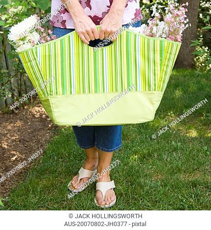 Mid section view of a mature woman holding flowers in a bag