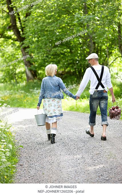 Mature couple holding hands and walking through graveled road