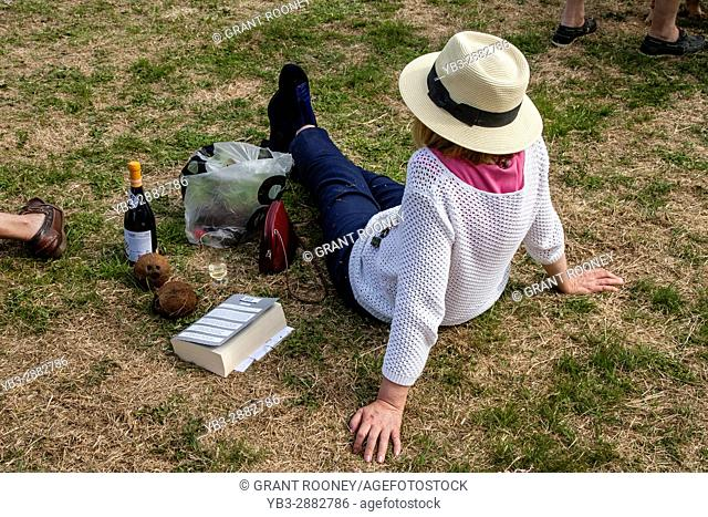 A Woman Sitting Down On The Rectory Field At The Jevington Fete, Jevington, East Sussex, UK